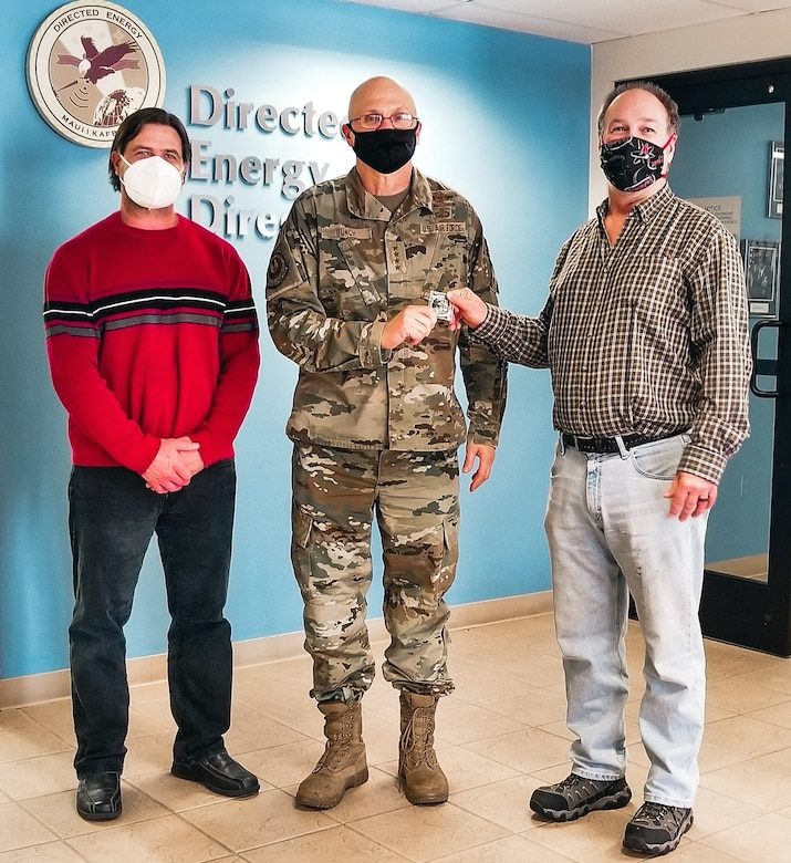 While visiting Kirtland Air Force Base, N.M., Gen. Arnold W. Bunch Jr., commander, Air Force Materiel Command, presented his coveted challenge coin to Pete Finlay (right) and Joe Volza (left) to recognize their team's contributions in advancing the Air Force's base defense priorities. (Courtesy photo)
