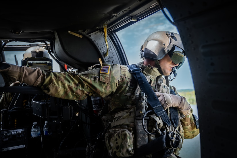 An aircrew member looks out the door of a helicopter during a flight.