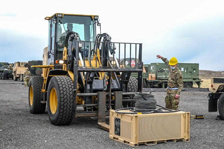 An Airman guides an electrical control unit onto a forklift.