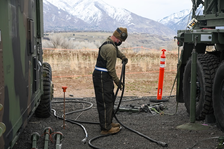 An Airman holding an electric cable.