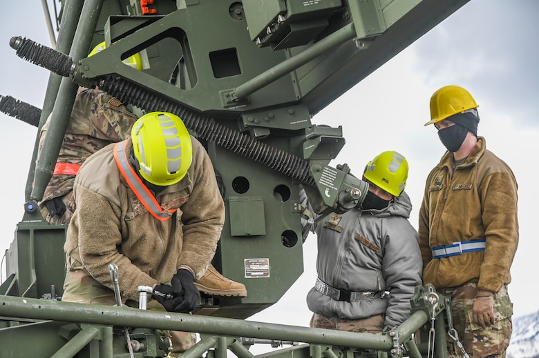 Three Airman working on an AN/TPS-75 radar system.
