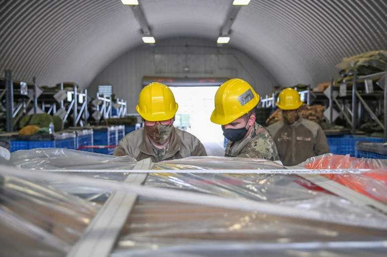 Two Airmen tight down straps on cargo cases.