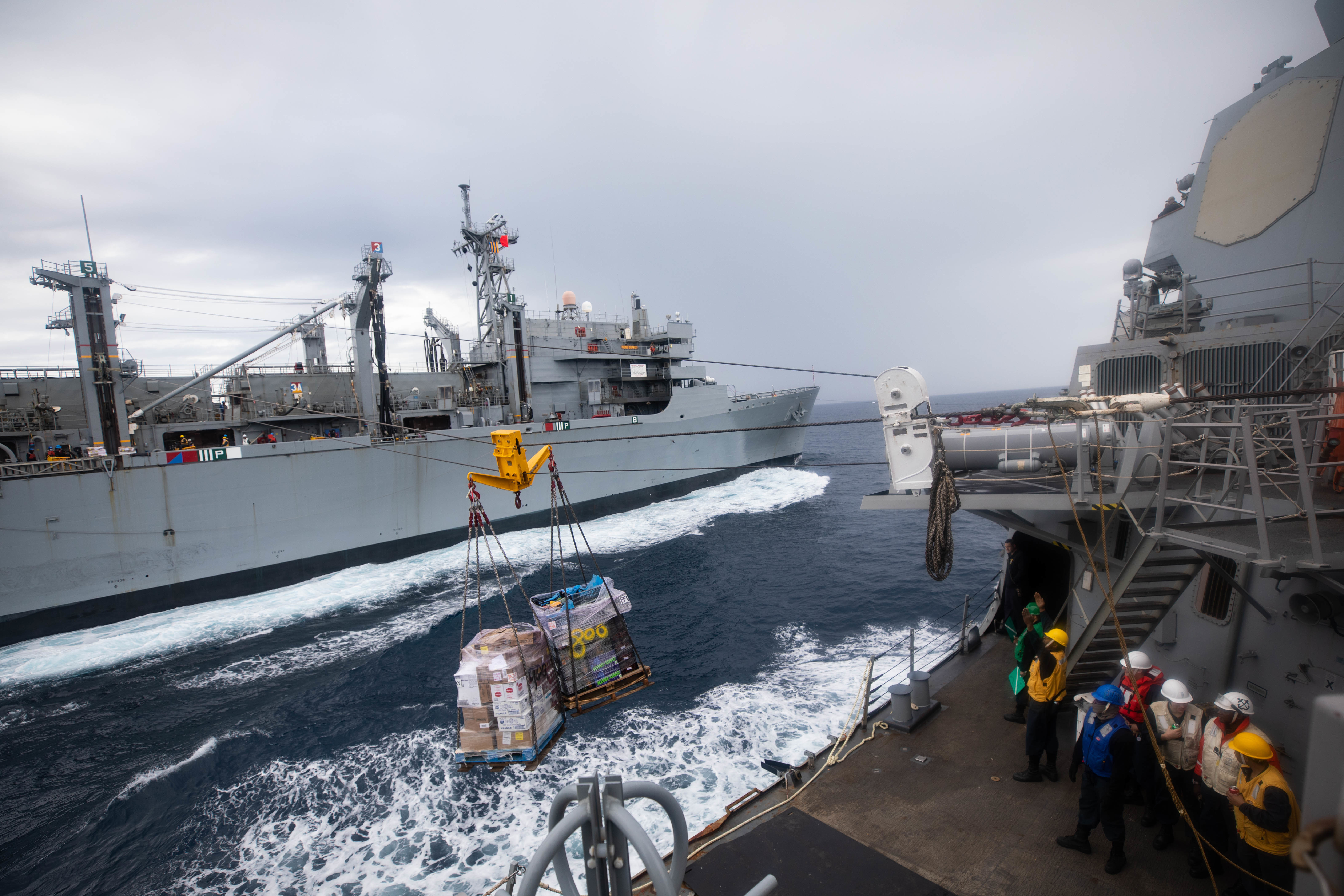 The Arleigh Burke-class guided-missile destroyer USS Roosevelt (DDG 80), right, receives pallets of food stores during a replenishment-at-sea with the fast combat support ship USNS Supply (T-AOE 6), not pictured.
