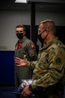 """U.S. Air Force Capt. Spencer """"Boca"""" Rhoton, left, a 13th Fighter Squadron F-16 Fighting Falcon pilot, listens to Col. Jesse J. Friedel, right, the 35th Fighter Wing commander speak at Misawa Air Base, Japan, April 7, 2021. Rhoton was hand-selected to accompany the 13th FS on the recent six-jet Agile Combat Employment-style deployment to Chitose during 5th Air Force's Exercise PACIFIC RONIN and was named an Exercise """"Superior Performer"""" by the 5th AF exercise team.. (U.S. Air Force photo by Airman 1st Class China M. Shock)"""