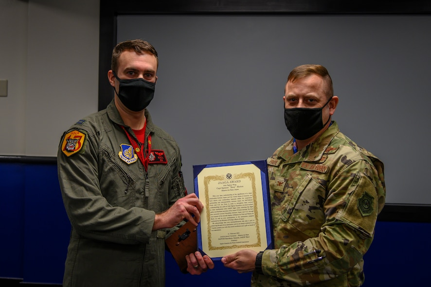 """U.S. Air Force Capt. Spencer """"Boca"""" Rhoton, left, a 13th Fighter Squadron F-16 Fighting Falcon pilot, receives the Japan-American Air Force Goodwill Association (JAAGA) award from Col. Jesse J. Friedel, right, the 35th Fighter Wing commander at Misawa Air Base, Japan, April 7, 2021. The JAAGA recognized Rhoton for his dedicated time to building a strong bond and partnership with the Japanese members at Misawa Air Base, Japan, April 9. (U.S. Air Force photo by Airman 1st Class China M. Shock)"""