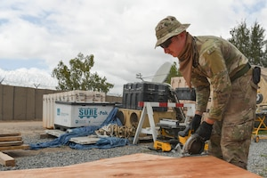 U.S. Air Force Staff Sgt. Garison Dollar, 786th Civil Engineer Squadron structural specialist, prepares to cut a wall cutout March 23, 2021, at Camp Simba, Kenya. The 786th CES deployed to Camp Simba to help expand the base, as well as to provide the base with improvements to quality of life.