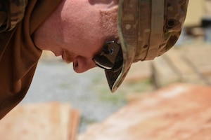 U.S. Air Force Staff Sgt. Garison Dollar, 786th Civil Engineer Squadron structural specialist, cuts a wall template for a tent March 23, 2021, at Camp Simba, Kenya. The 786th CES provided Camp Simba with building new structures, water systems and maintenance so the base can provide continued vigilance to the Combined Joint Task Force-Horn of Africa area of responsibility.