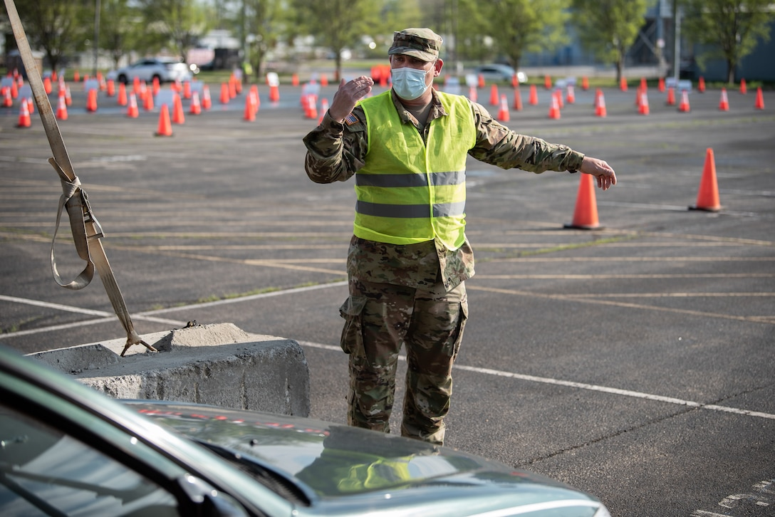 U.S. Army Sgt. Nicholas Wentworth of the Kentucky Army National Guard directs traffic at Kentucky's largest drive-through COVID-19 vaccination clinic at Cardinal Stadium in Louisville, Ky., April 12, 2021. More than 30 Soldiers and Airmen from the Kentucky Army and Air National Guard are providing direct support to the clinic, which can vaccinate up to 4,000 patients a day. (U.S. Air National Guard photo by Dale Greer)