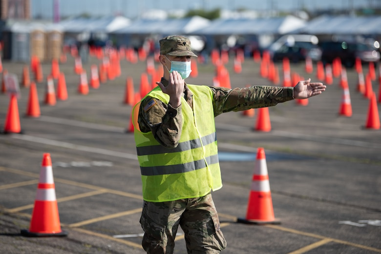 U.S. Army Spc. Logan Kilmon of the Kentucky Army National Guard directs traffic at Kentucky's largest drive-through COVID-19 vaccination clinic at Cardinal Stadium in Louisville, Ky., April 12, 2021. More than 30 Soldiers and Airmen from the Kentucky Army and Air National Guard are providing direct support to the clinic, which can vaccinate up to 4,000 patients a day. (U.S. Air National Guard photo by Dale Greer)