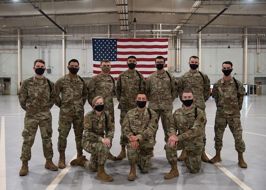 Student drill team members from various squadrons, pose for a photo after participating in a recorded drill routine.
