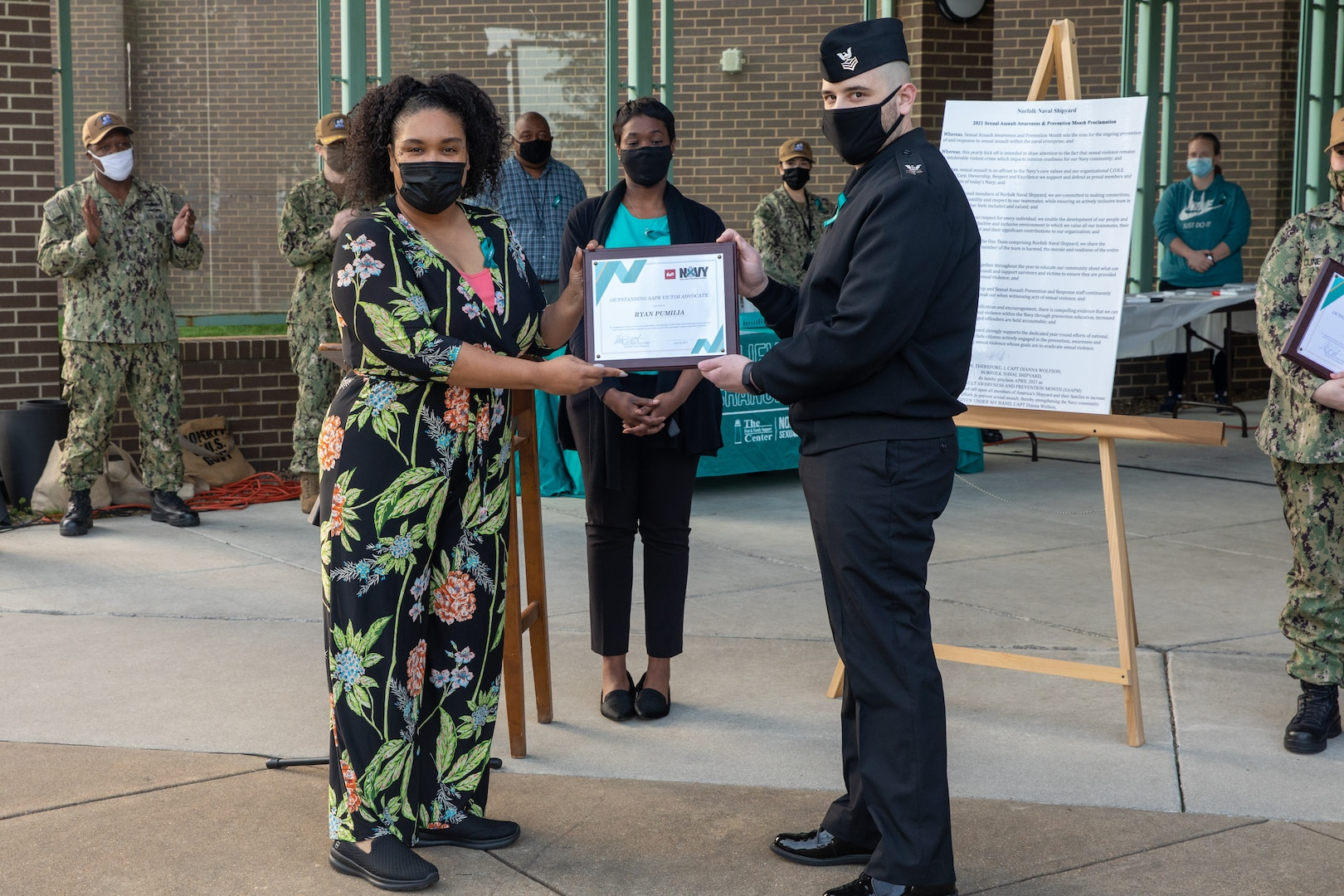 Four Sexual Assault Prevention and Response (SAPR) Victim Advocates (VAs) were selected as SAPR representatives of the year. Here, and Naval Network Warfare Command's (NETWARCOM) IT2 Ryan Pumilia receives an award from Norfolk Naval Shipyard's (NNSY) Sexual Assault Response Coordinator (SARC) Shalise Bates-Pratt and Federal Women's Program (FWP) president Aiya Williams.