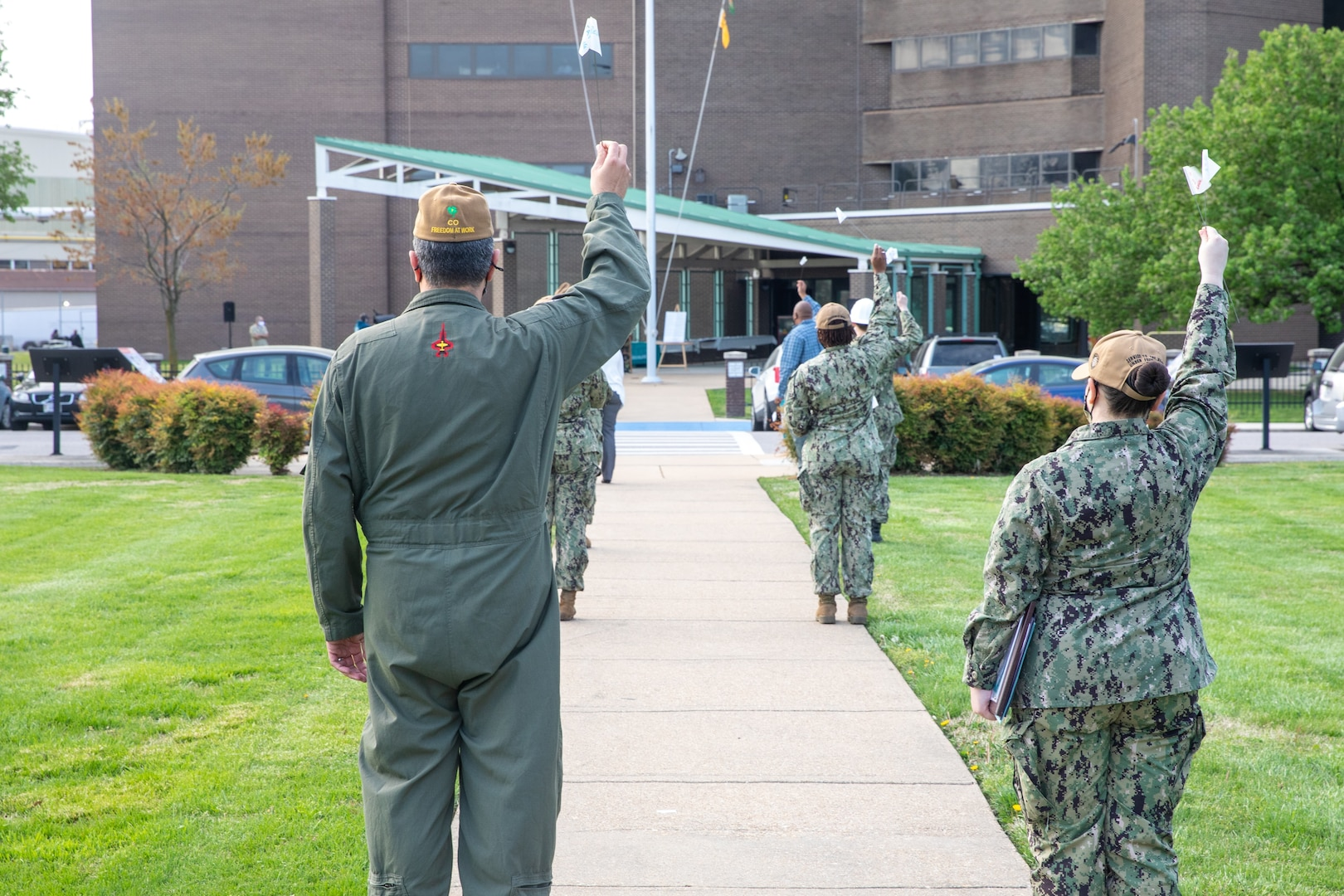 Norfolk Naval Shipyard (NNSY) team members hold white flags with hand written messages of support in the air marking a moment of silence during the shipyard's Sexual Assault Awareness and Prevention Month (SAAPM) kickoff event April 9.