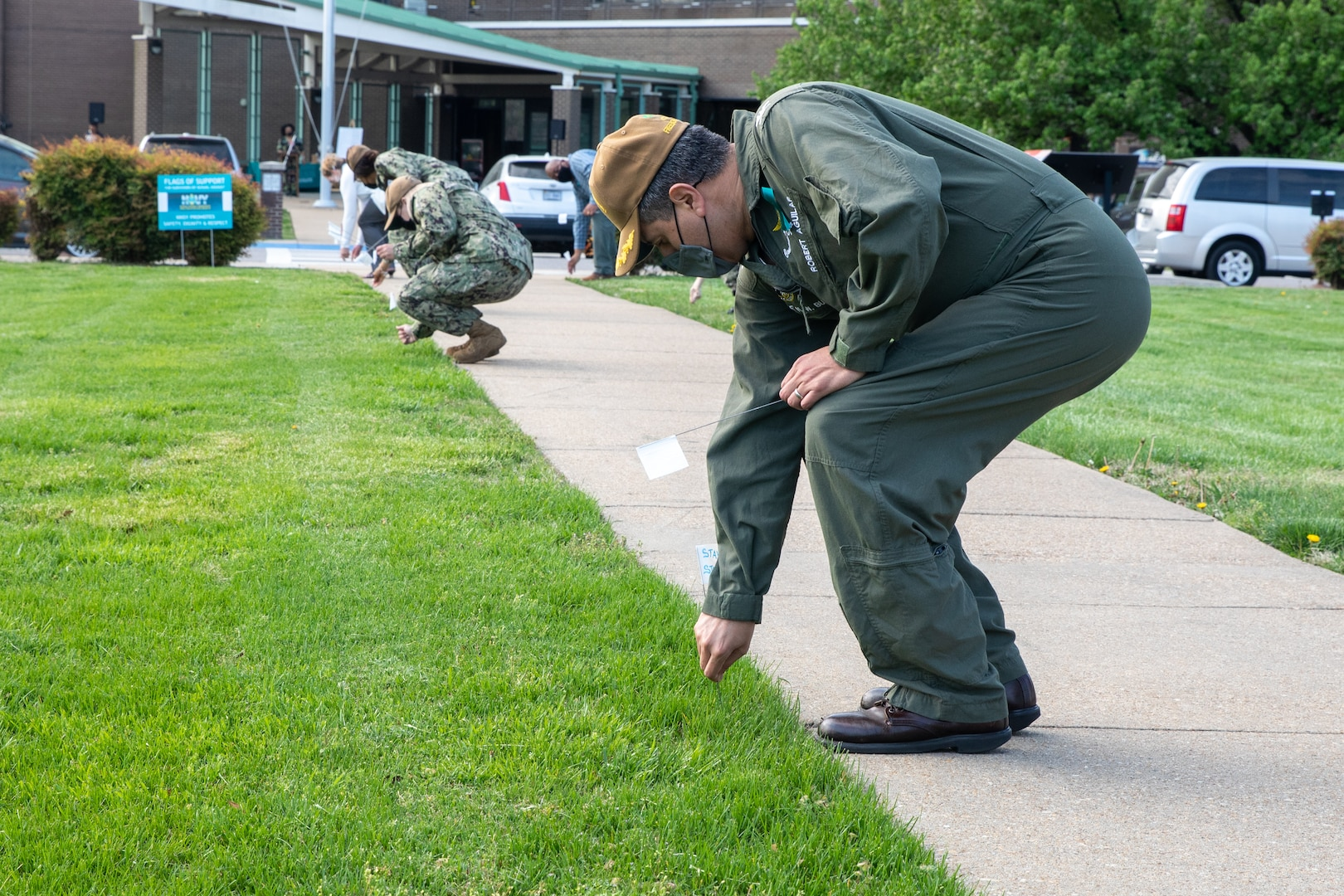 USS George H.W. Bush (CVN 77) Commanding Officer Capt. Robert Aguilar plants a flag of support in the ground outside of Norfolk Naval Shipyard's Engineering and Management Building during the shipyard's Sexual Assault Awareness and Prevention Month (SAAPM) kickoff event April 9.