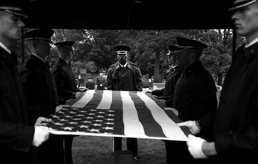 Airmen with the United States Air Force Honor Guard prepare to fold the American flag during a funeral honoring the late Col. Noel Elmer Hoblit on May 21, 2015 at Arlington National Cemetery. Col. Hoblits two sons, U.S. Air Force Col. Jerry Hoblit (ret.) and Lt. Col. (ret.) Fred Hoblit, remembered the life of their father during a funeral with family and friends at the Arlington National Cemetery. Col. Hoblit perished in an airplane crash near Alaska on Nov. 22, 1952. Personnel assigned to the Joint Recovery Prisoner of War Missing In Action team, located, identified and returned Col. Hoblit to his family for a ceremony with honor.