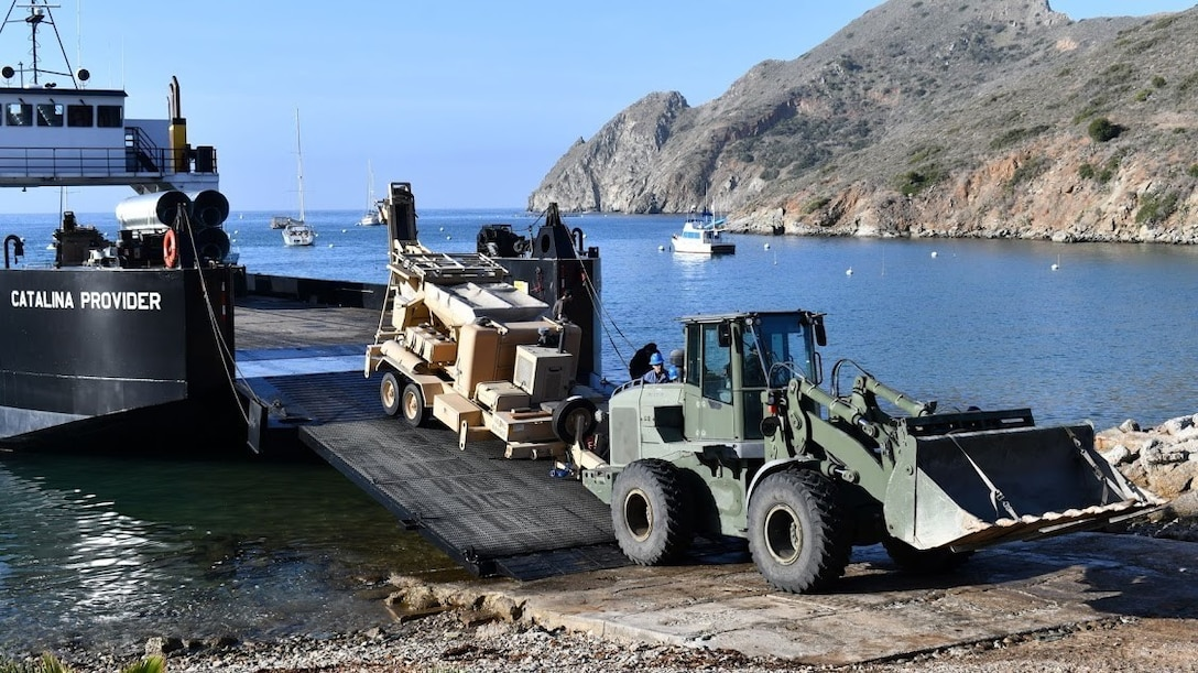 Marines with Marine Wing Support Squadron (MWSS) 373, Marine Aircraft Group 11, 3rd Marine Aircraft Wing, unload equipment from a barge at Catalina Island, California, April 11, 2021. The disembarkation of utility and engineer assets marked the beginning of the road reconstruction project. (Courtesy photo by Jessica Boudevin/Catalina Island Conservancy)