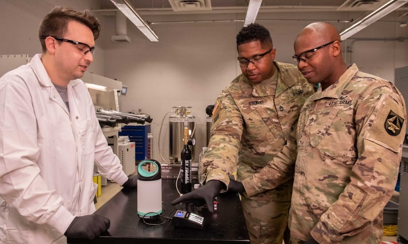 Soldiers stand with a researcher in a science laboratory.