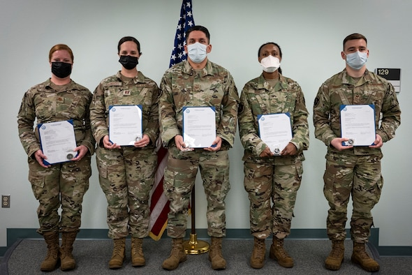 Five medical Airmen hold awards in front of U.S. flag.
