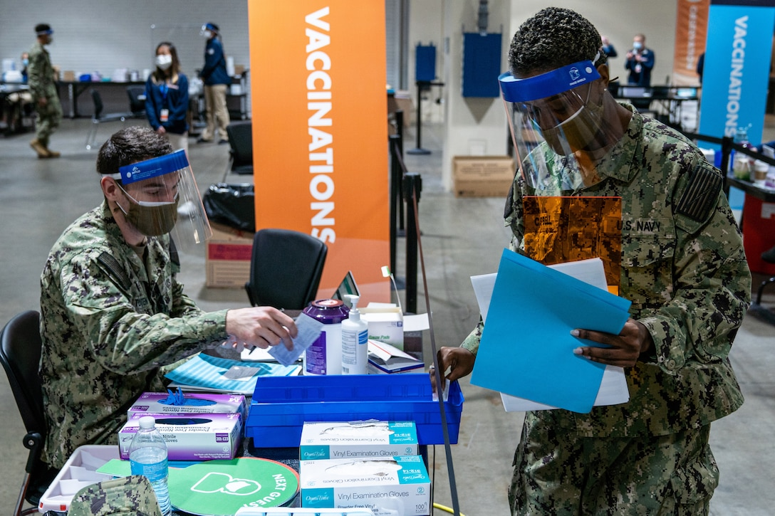 Navy sailors wearing face masks refill COVID-19 vaccine supplies.