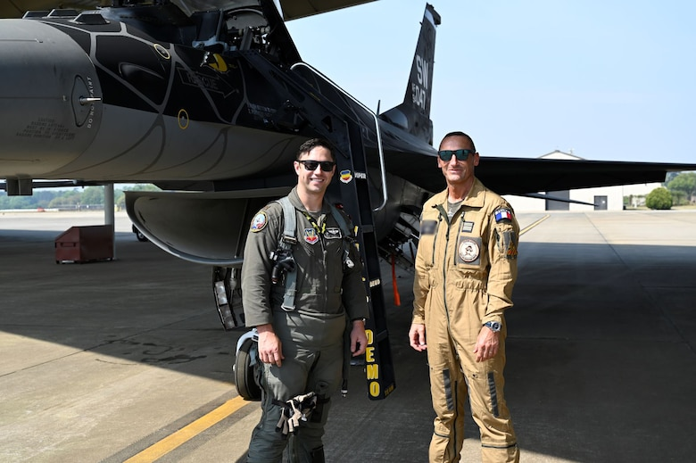 "Maj. Garret Schmitz, F-16 Viper Demonstration Team commander and pilot, poses with a member from the French Air and Space Force at Shaw Air Force Base, South Carolina, April 8, 2021. Senior military representatives from nine countries traveled to Shaw AFB this week to participate in ""Coalition Week,"" a series of events focused on showcasing 9th Air Force's (U.S. Air Forces Central) ability to distribute operations and command and control airpower from more than one location. (U.S. Air Force photo by Tech. Sgt. E'Lysia Wray/Released)"