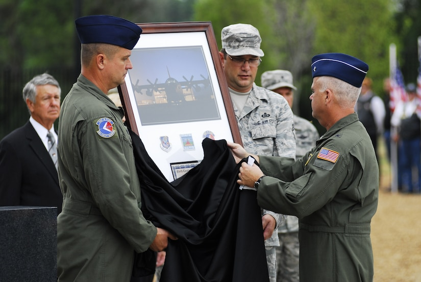 """Brig. Gen. Tony McMillan, 145th Airlift Wing commander, unveils a picture of C-130 tail number 1458, retiring the number """"7"""" from Modular Airborne Fire Fighting System future missions, during the memorial honoring four fallen airmen who died, July 1, 2012, while fighting forest fires from a Modular Airborne Fire Fighting (MAFFS) equipped C-130H aircraft in southwestern South Dakota."""