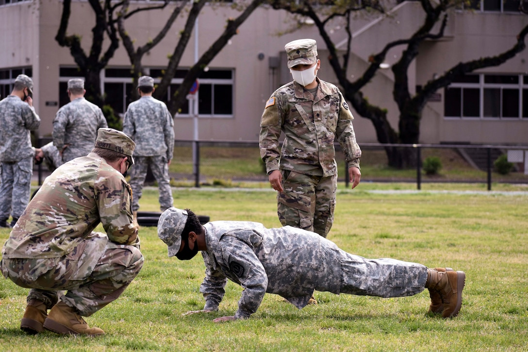 A soldier performs a pushup in front of other soldiers.