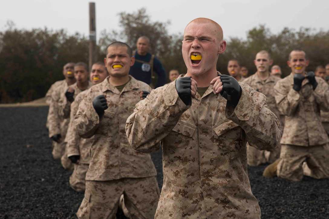 A group of Marine Corps recruits kneel on the ground while raising their hands.
