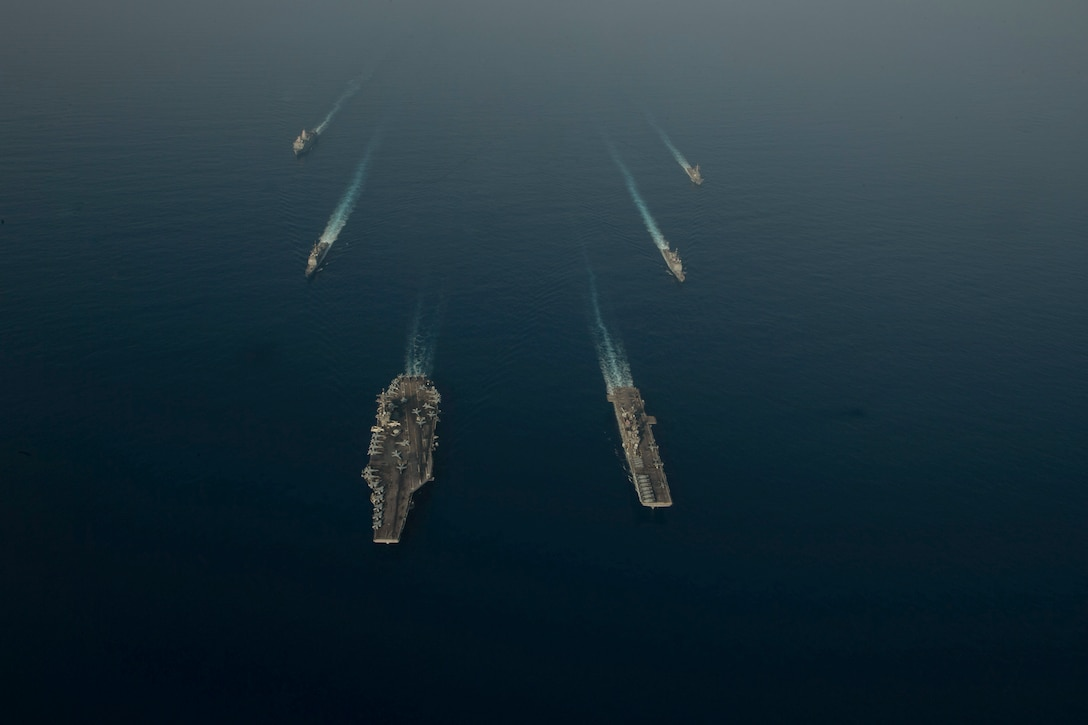 Ships sail in formation in the sea.
