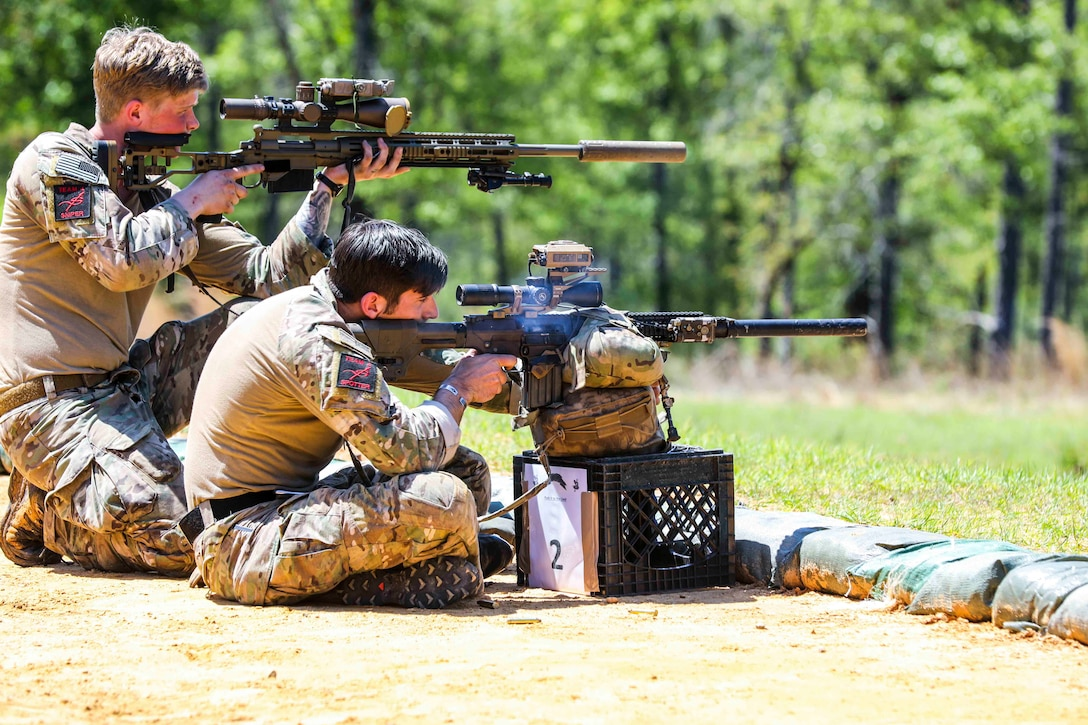 A soldier kneels next to another soldier who is sitting on the ground, both firing weapons at a target.