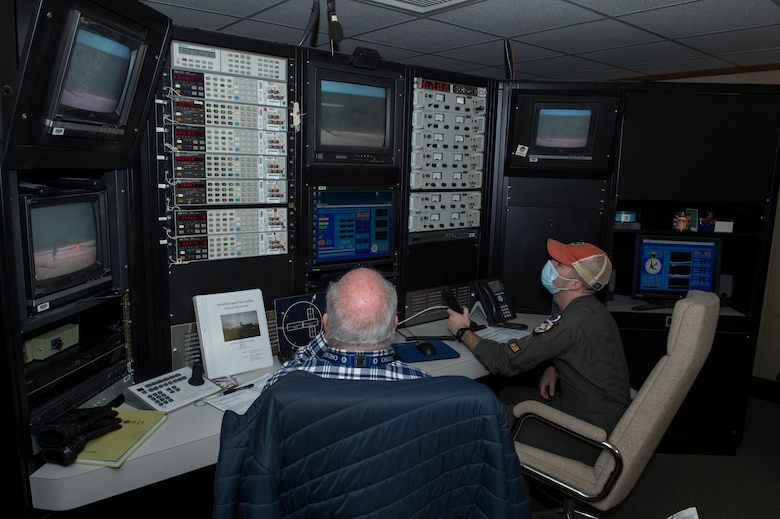 Gary Peddecord, 812th Aircraft Instrumentation Test Squadron, and Capt. Cameron Clites, Air Force Test Pilot School class 20-B student, monitor an engine test run at the Installed Engine Test Facility Horizontal Thrust Stand control room at Edwards Air Force Base, California, March 5. (Air Force photo by Joshua Miller)