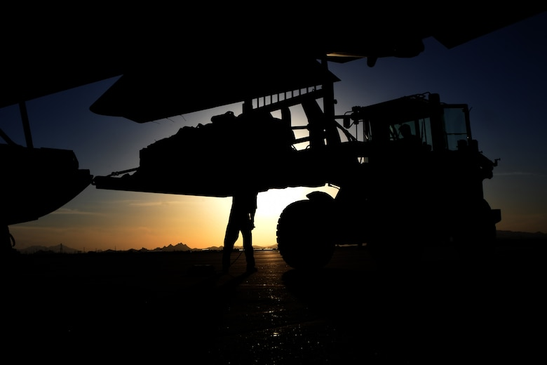 A photo of a forklift carrying a load at sunset