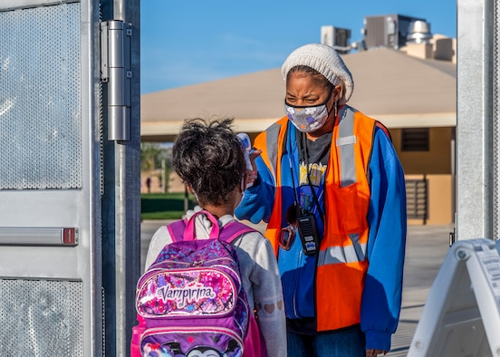 A Bailey Elementary School faculty member checks a student's temperature before entering school premises during the first day of physical in-person learning and grand reopening of Bailey Elementary School on Edwards Air Force Base, California, April 12. (Air Force photo by Giancarlo Casem)