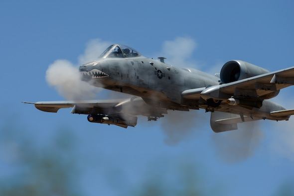 A photo of a flying aircraft with smoke around it.