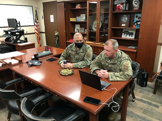 Two Airmen participate in a virtual meeting.