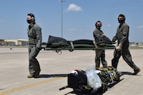 The 433rd Aeromedical Evacuation Squadron reserve citizen Airmen load medical equipment on a C-130 J Hercules during a joint training exercise at Joint Base San Antonio-Lackland, Texas, April 8, 2021. The medical flight crew simulated the loading of medical equipment to assist in contaminated patient transport. (U.S. Air Force photo by Senior Airman Brittany Wich)
