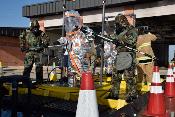 The 433rd Civil Engineer Squadron and Joint Base San Antonio Fire Department firefighters brush and wash the contaminates off of firefighters in hazardous material suits during a joint training exercise at Joint Base San Antonio-Lackland, Texas, April 8, 2021. The 433rd CES and JBSA Fire Department firefighters wore mission oriented protective posture gear and HAZMAT suits to protect themselves against simulated contaminates from patients and personnel. (U.S. Air Force photo by Senior Airman Brittany Wich)