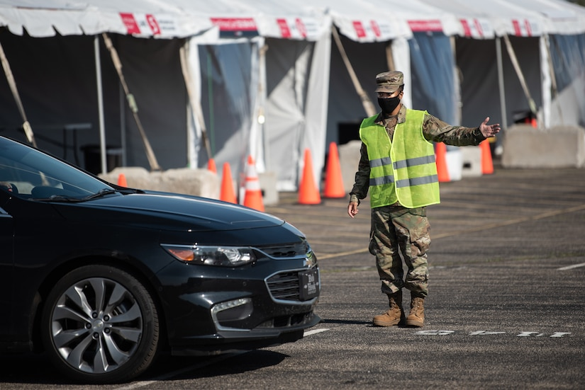 U.S. Air Force Senior Airman Morgan Thomas of the Kentucky Air National Guard directs traffic at Kentucky's largest drive-through COVID-19 vaccination clinic at Cardinal Stadium in Louisville, Ky., April 12, 2021. More than 30 Soldiers and Airmen from the Kentucky Army and Air National Guard are providing direct support to the clinic, which can vaccinate up to 4,000 patients a day. (U.S. Air National Guard photo by Dale Greer)