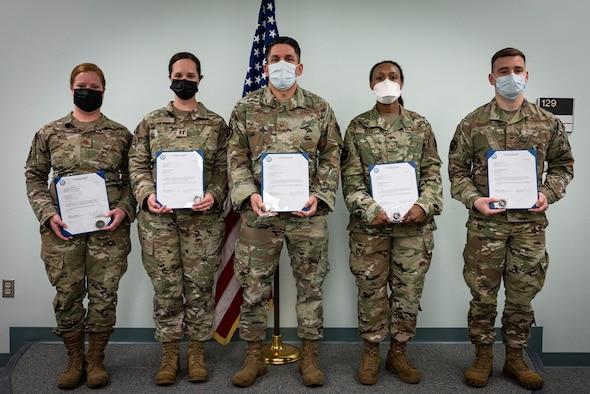 Five medical Airmen hold awards in front of U.S. flag.