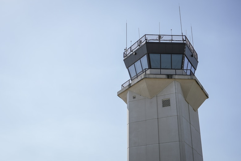 Control tower juxtaposed against blue sky.
