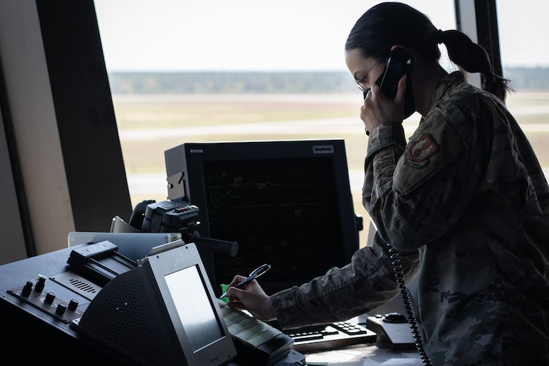Female Airman answers phone and writes with a pen.