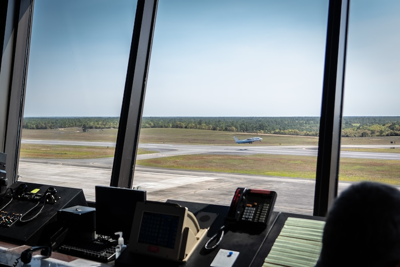 Aircraft takes off from runway as seen through window of control tower.