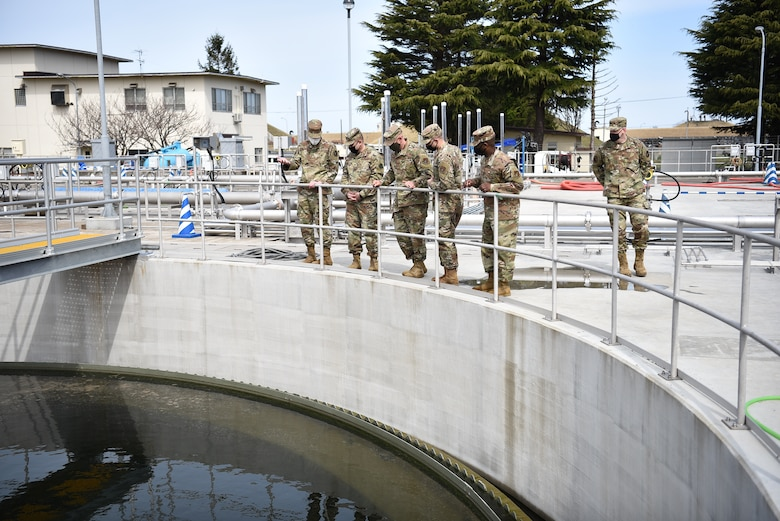 Group of military members look into a clarifying tank.