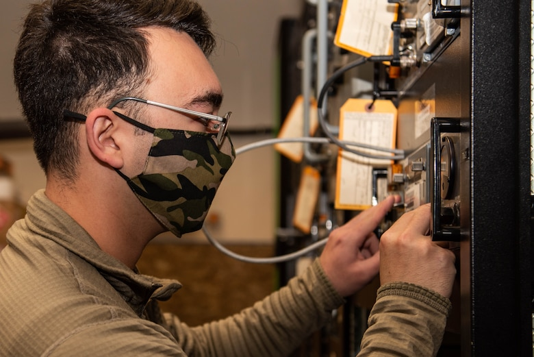 A RAWS Airman works to fix an wall-mounted radio transmitter