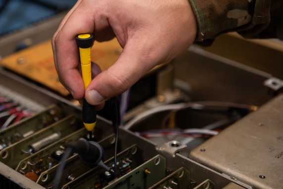A closeup of a an Airman's hand fixing a delicate part of a radio
