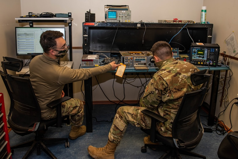 Two seated Airmen repair radio equipment on a workbench