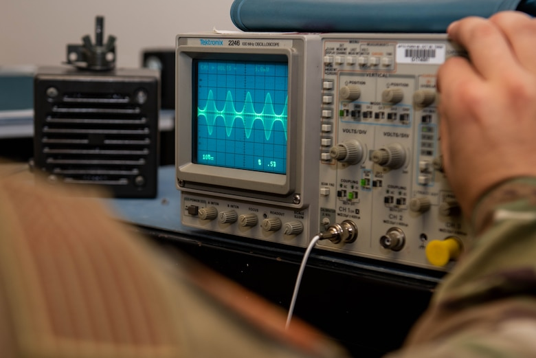 An Airman works with a piece of radio equipment