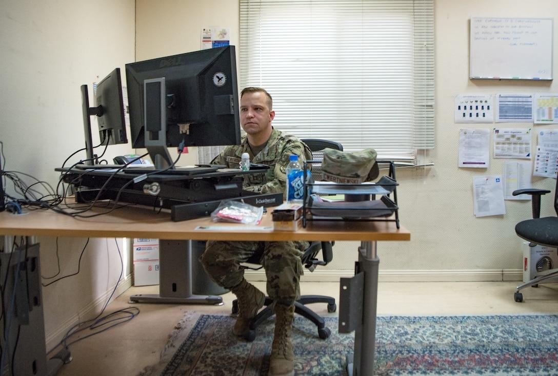 a man works at a computer at a desk