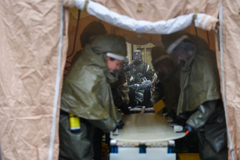 U.S. Airmen from the 31st Fighter Wing perform decontamination procedures during a base defense readiness exercise at Aviano Air Base, Italy, April 12, 2021. The training was conducted to assess and improve the team's proficiency in implementing and executing proper decontamination procedures in the event of a chemical, biological, radiological or nuclear incident. (U.S. Air Force photo by Senior Airman Ericka A. Woolever)