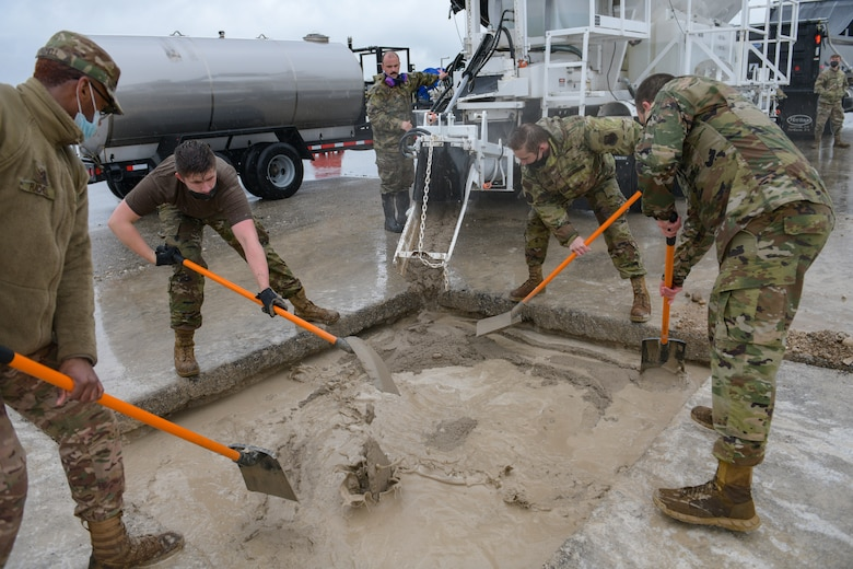 Airmen assigned to the 31st Civil Engineer Squadron spread concrete mixture into a crater during a base defense readiness exercise at Aviano Air Base, Italy, April 12, 2021. During Rapid Airfield Damage Repair (RADR) operations on the flightline, Airmen repaired 18 small craters in approximately eight hours. (U.S. Air Force photo by Airman 1st Class Brooke Moeder)
