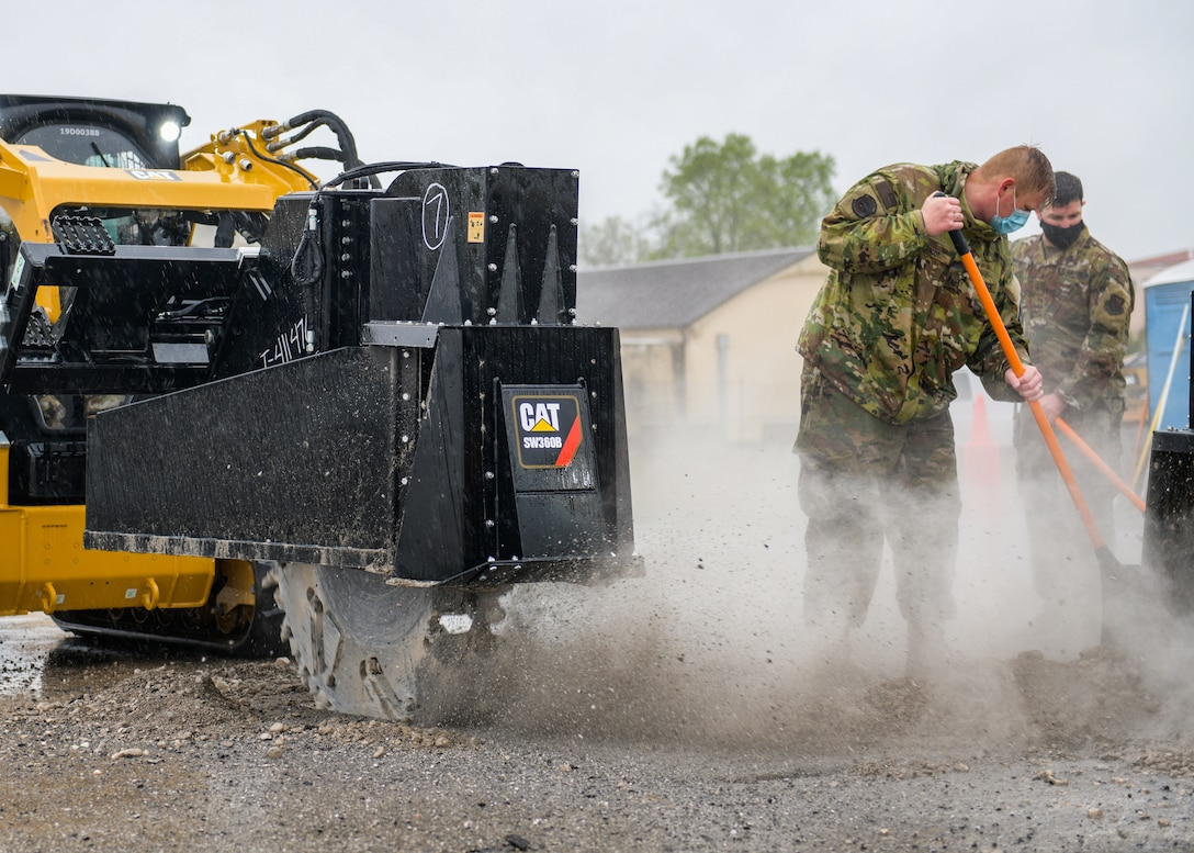 Tech. Sgt. Elliott Bercot, 31st Civil Engineer Squadron water and fuels system maintenance (WFSM) member, left, and Master Sgt. James Porter, 31st CES WFSM section chief, clear debris from a 60-inch wheel-saw during a base defense readiness exercise at Aviano Air Base, Italy, April 12, 2021. The 31st CES conducted Rapid Airfield Damage Repair (RADR) operations on the flightline and executed emergency operations center (EOC) events, fire protection, airfield damage assessment and more. (U.S. Air Force photo by Airman 1st Class Brooke Moeder)
