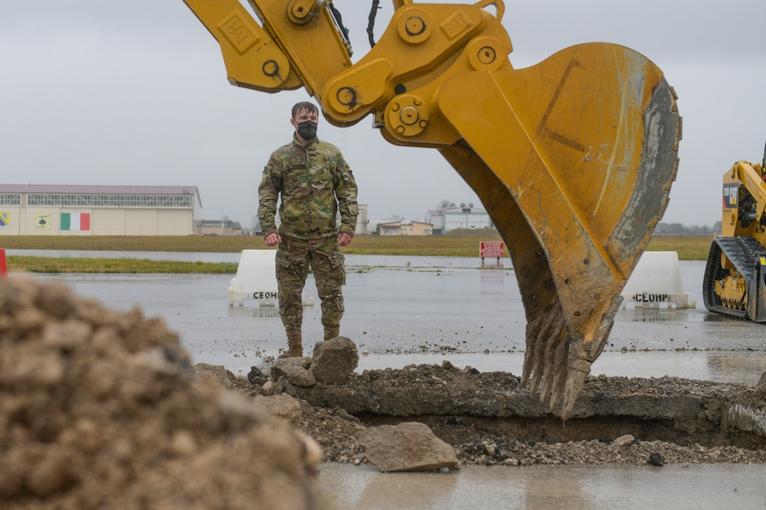 Airman 1st Class Brenden Kazmierczak, 31st Civil Engineer Squadron water and fuels technician, watches an excavator dig a crater during a base defense readiness exercise at Aviano Air Base, Italy, April 12, 2021. The 31st CES conducted Rapid Airfield Damage Repair (RADR) during the exercise, creating a stable base for a concrete mixture to pour into the crater. (U.S. Air Force photo by Airman 1st Class Brooke Moeder)